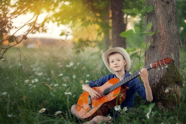 Adorable boy with guitar, relaxing in the park. kid sitting on a grass in summer day
