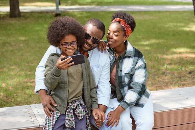 Очаровательный мальчик со смартфоном фотографирует свою семью во время отдыха в парке