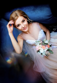 Adorable bride in rich wedding dress rests in a large soft blue chair