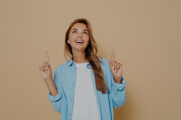 긴 생머리를 가진 사랑스러운 브루네트 여성은 캐주얼한 흰색 티셔츠와 파란색 셔츠를 입고, 빈 카피 공간을 위쪽으로 가리키고, 천장에 무언가를 주목하고, 베이지색 벽에 기대어 서 있습니다.