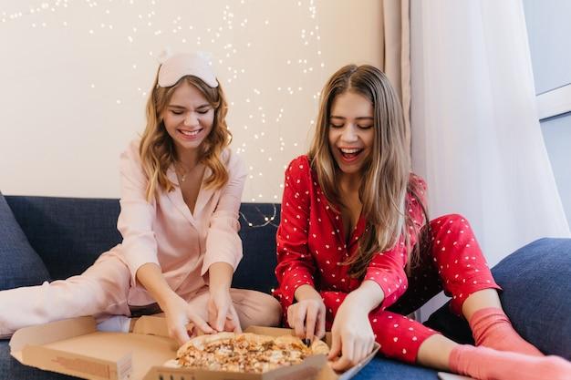 아침에 피자를 먹는 귀여운 양말에 사랑스러운 갈색 머리 소녀. 잠 옷에서 아침 식사를하는 동안 포즈를 취하는 두 여자의 실내 사진.