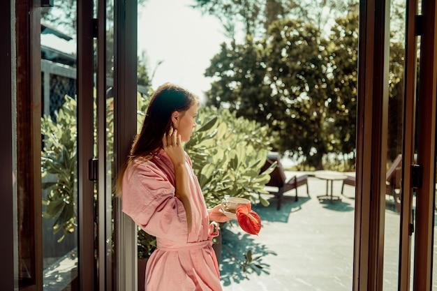 An adorable brunette in a pink robe stands with a cup of tea and a red flower. the of rest and relaxation.