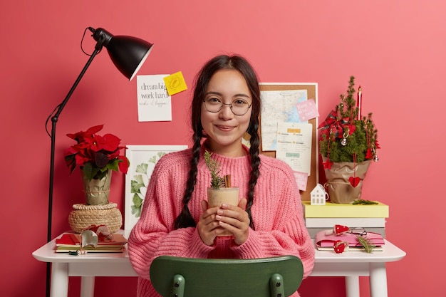 Adorable brunette teenage girl dressed in winter sweater, holds eggnog with cinnamon, wears round spectacles, sits at chair near workplace, pink color prevails.