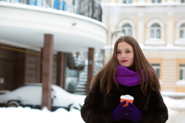 커피 한잔과 함께 거리에서 포즈를 취하는 겨울 의류를 입은 사랑스러운 갈색 머리 여자