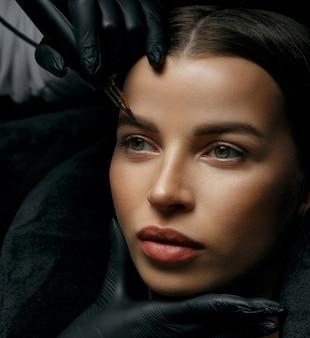 Adorable brunette woman having brow permanent procedure at the beauty studio. closeup shot