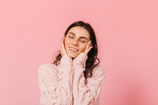 愛らしいブルネットの女性は目を閉じて優しく微笑む。ピンクのスタジオでポーズをとる暖かいセーターの女性。