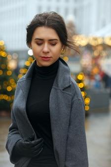 愛らしいブルネットの女性は、クリスマスに飾られた街で雨の日に歩く流行のコートを着ています