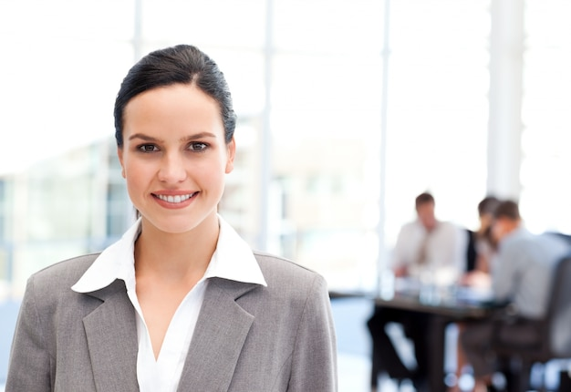 Adorable businesswoman standing in front of her team while working