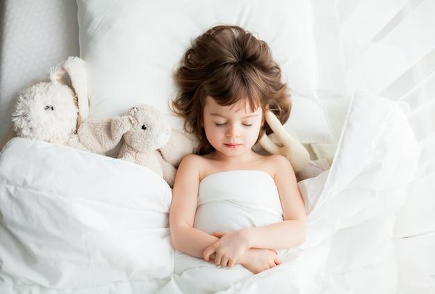 Очаровательная спокойная маленькая девочка спит в белой кровати с игрушками-кроликами рядом с ней