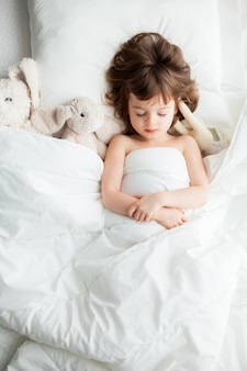 Adorable calm little girl sleeping in white bed with rabbit toys