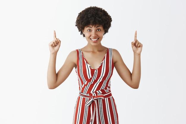 愛らしい屈託のない、幸せなアフリカ系アメリカ人の巻き毛のヘアスタイルを上げられた人差し指で上向きにし、コピースペースに最適な場所を提供しながら楽しく笑顔
