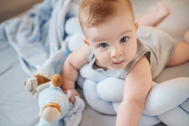 寝室のベッドの上の胃の上に横たわる大きな青い目を持つ愛らしい白人男の子