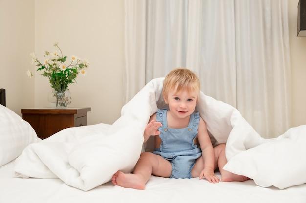 愛らしい白人のブロンドの女の赤ちゃんの遊びは、ベッドの上の暖かい毛布の下の白いシーツで楽しんでください冷たい子供