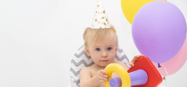 Adorable caucasian blonde baby girl, sitting at high chair by colorful balloons wearing birthday hat playing with toy pyramidion on light background.kid party,child game concept.copy space for text.