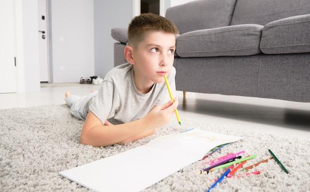 自宅の部屋の机に座って鉛筆で虹を描く小学生の愛らしい白人少年。セレクティブフォーカスの画像