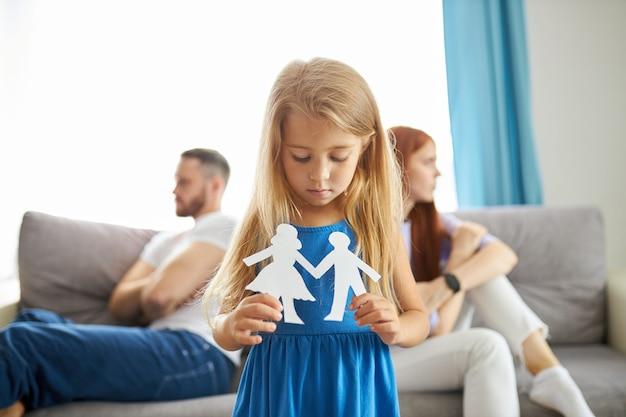 Adorable caucasian child girl between depressed parents