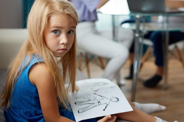 Очаровательная кавказская девочка держит рисунок родителей, разлученных