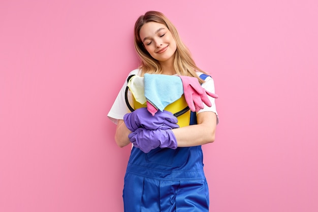 Adorable caucasian female in blue work uniform stand with bucket and rags posing isolated on pink wall