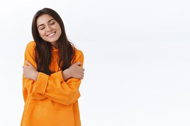 Очаровательная кавказская женщина-брюнетка в оранжевой толстовке с капюшоном, закрывает глаза и мило улыбается, обнимает себя, обнимает, чувствуя уют, мягкая толстовка с капюшоном, белая стена