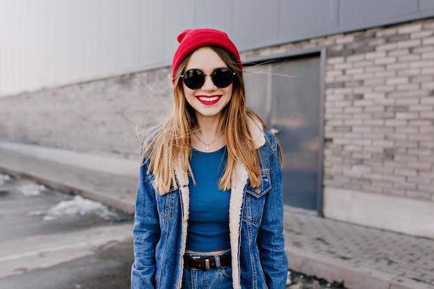 通りに立って笑っている黒いサングラスの愛らしい白人の女の子。春の日に歩き回るデニムジャケットの魅力的な白人女性。