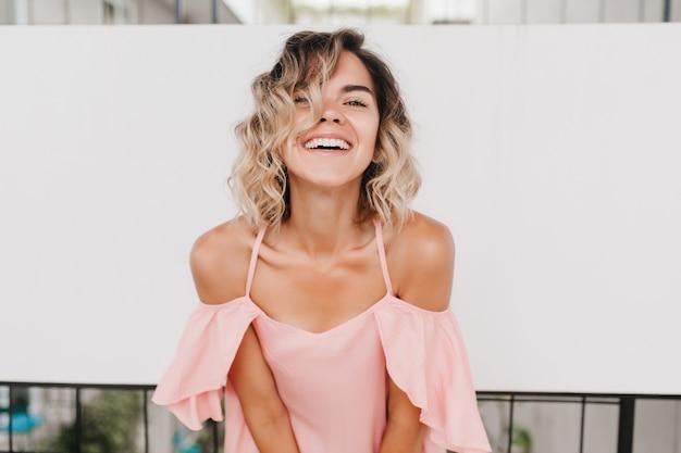 Очаровательная кавказская девушка в розовой одежде, смеясь в хороший день. портрет радостной дамы с волнистой прической.