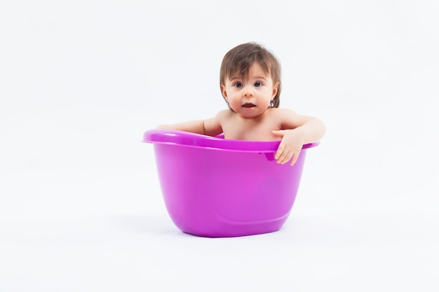 Adorable caucasian girl taking bath in purple tub on white