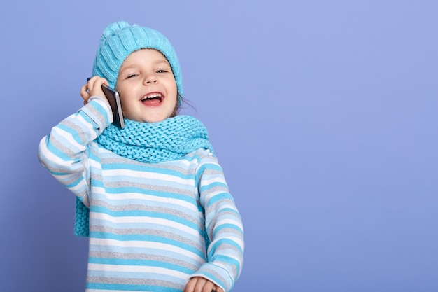 Adorable caucasian little girl talking via phone with her friend isolated over blue