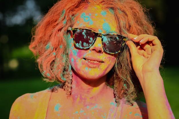 마른 holi 페인트로 덮여 안경을 쓰고 사랑스러운 백인 모델