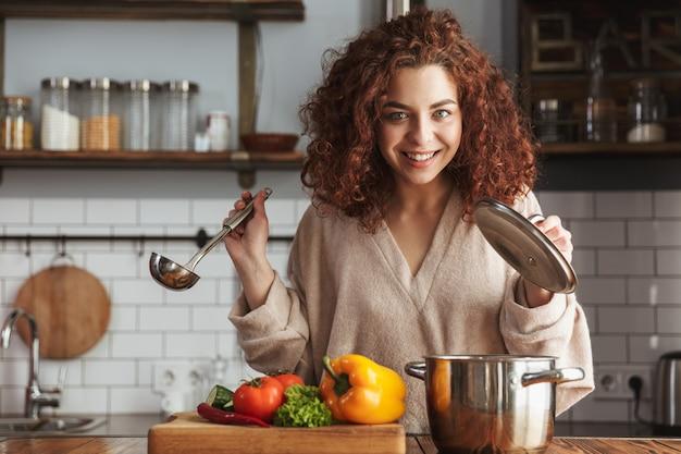 Очаровательная кавказская женщина, держащая кухонную ложку, пока ест суп со свежими овощами на кухне дома