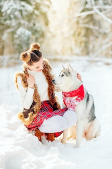 Adorable caucasian woman spending time outdoor enjoying the frosty weather with her husky pet. photo of pretty young lady in winter outfit, piercing look of a girl and a dog