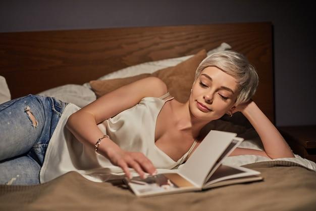 雑誌の写真を見て、夜のリラックスした時間を楽しんで、休憩をとって、ベッドに横たわっている金髪の短い髪の愛らしい白人女性