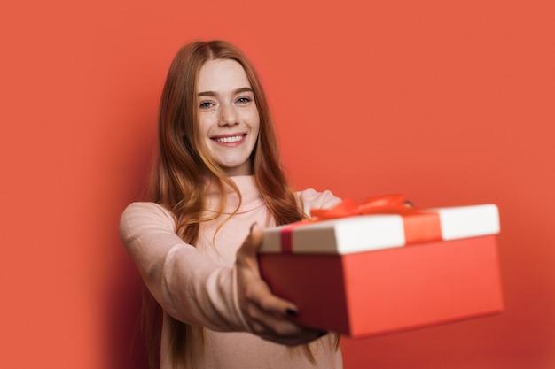 そばかすと赤い髪の愛らしい白人女性がカメラに笑顔のプレゼントボックスを与えています