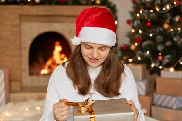 愛らしい魅力的な陽気な女性はギフトボックスを持って、中身を推測し、リボンに指を置き、ボックスを見て、暖炉とクリスマスツリーに座っています