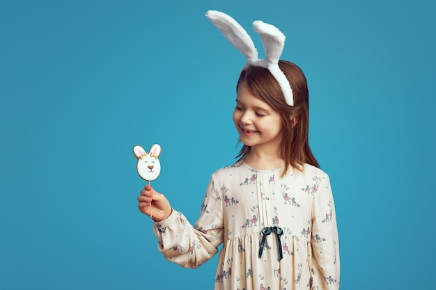 Очаровательная очаровательная девушка улыбается и держит печенье в форме кролика с кроличьими ушками над синей стеной
