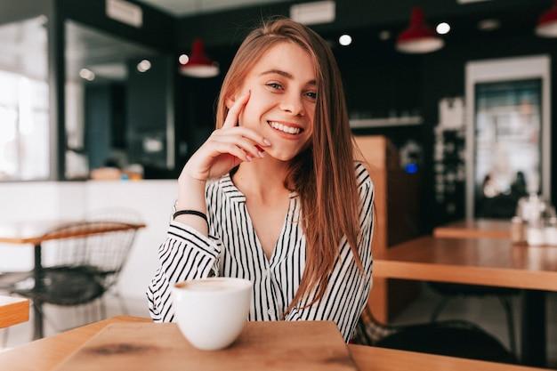 Очаровательная очаровательная дама с длинными волосами в модной блузке сидит в кафетерии с большой улыбкой