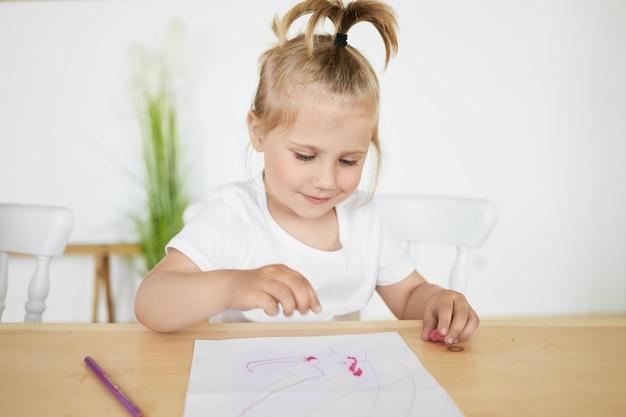 Очаровательная очаровательная маленькая девочка с хвостиком сидит за партой в детском саду перед белой простыней, раскрашивает или лепит фигурки из пластилина или глины, с счастливым радостным выражением лица