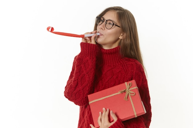 Adorable charming young female wearing speactales and pullover blowing party horn while having fun, celebrating her birthday, holding gift in red box with ribbon. celebration and holiday concept