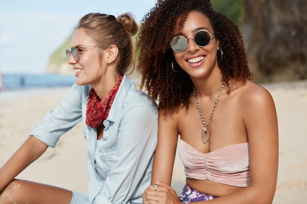 Adorable cheerful dark skinned african american woman in shades has positive expression, sits near her best friend or sister who looks into distance, spend free time on coastline. people and rest