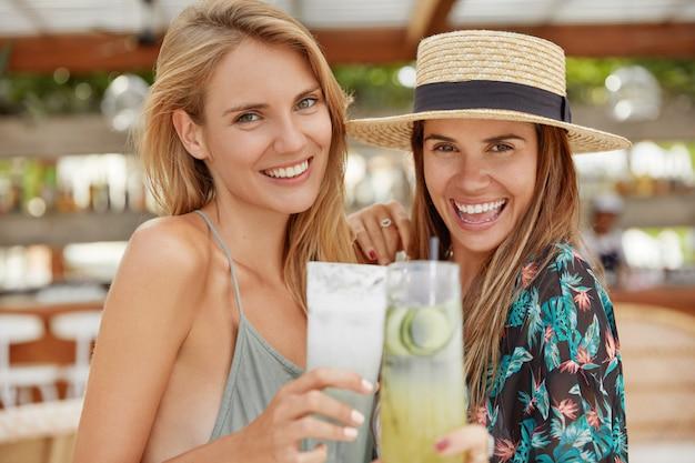 愛らしい陽気な女性は夏の帽子、ブラウスを着て、広い笑顔を輝かせ、カクテルのグラスをチャリンと鳴らし、夏休みの始まりを祝い、熱帯の国で休む機会を持つことを喜ぶ