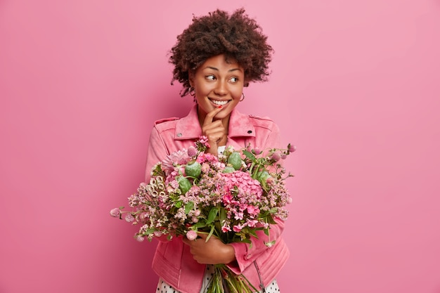 Adorable cheerful woman looks aside, gets bouquet of flowers, looks happily aside, poses