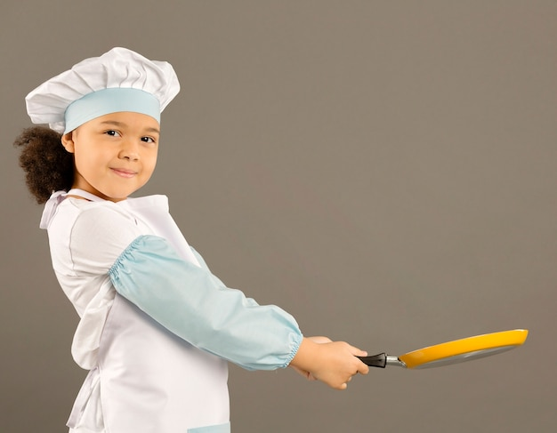 Adorable chef holding cooking pan