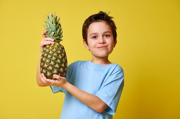 Прелестный ребенок мальчик, держащий ананас, позируя на желтом фоне с копией пространства.