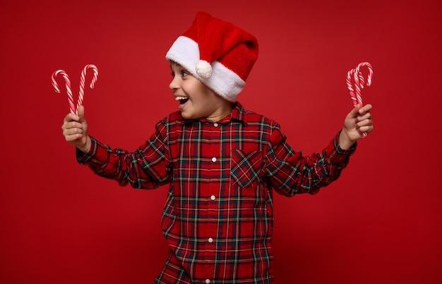 Очаровательный ребенок мальчик в красной клетчатой рубашке и шляпе санта-клауса, глядя на рождественские леденцы, полосатые сладкие леденцы в его руках, изолированные на красном фоне с копией пространства для рекламы