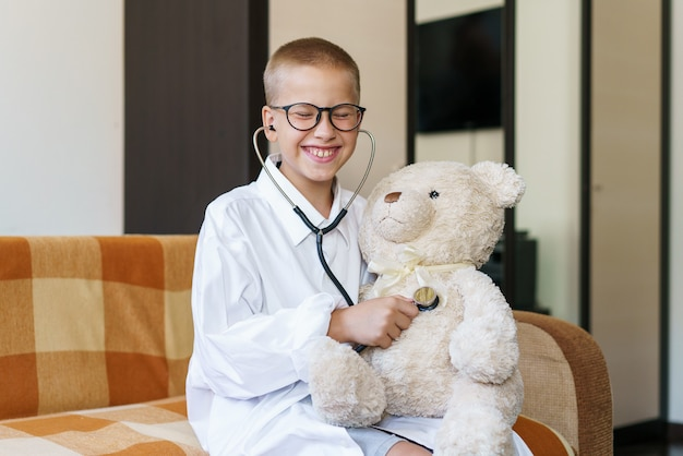 医者に扮した愛らしい子供が、自宅のソファでメガネをかけた幸せな男の子のぬいぐるみで遊んでいます...