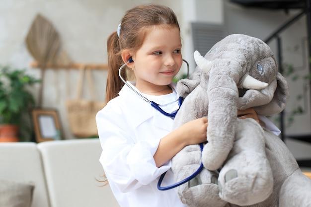 医者に扮した愛らしい子供がおもちゃの象と遊んで、聴診器で息をチェックします。