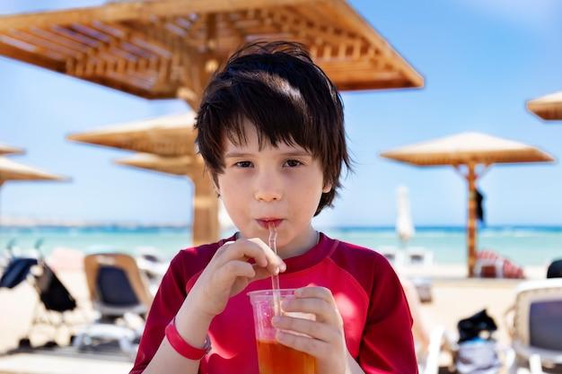 Очаровательный ребенок с удовольствием пьет вкусный коктейль из соломки в жаркий день на пляже.
