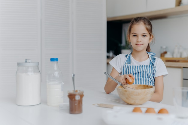 Adorable child enjoys cooking activity, breaks egg in bowl, whisks ingredients