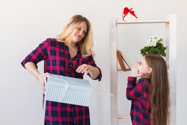 Очаровательная девочка с большой подарочной коробкой, дающей ее своей матери