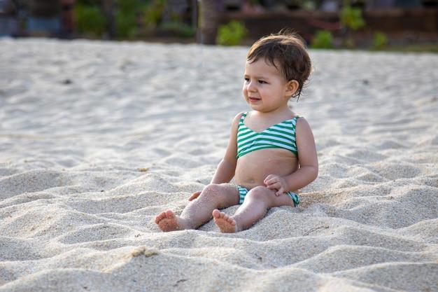 水着姿の愛らしい子供が日差しの中で砂浜に座っています