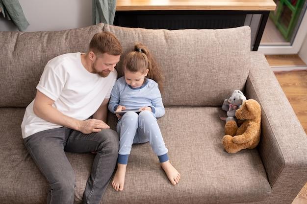 파란색 잠옷에 사랑스러운 아이와 그녀의 아버지는 소파에 편안하고 집에 머무르는 동안 태블릿에서 온라인 영화를보고